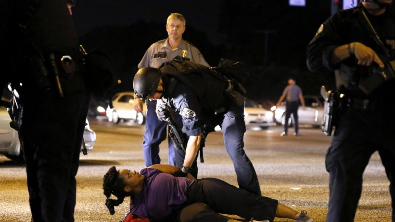 A woman protesting the shooting death of Alton Sterling is detained by law enforcement near the headquarters of the Baton Rouge Police Department in Baton Rouge. REUTERS/Jonathan Bachman