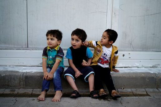 Three-year-old triplet brothers, Recep, Tayyip and Erdogan Yasin, named after Turkish President Recep Tayyip Erdogan, sit in front of a container at the Harran refugee camp in Sanliurfa province, Turkey, June 6, 2016. REUTERS/Umit Bektas