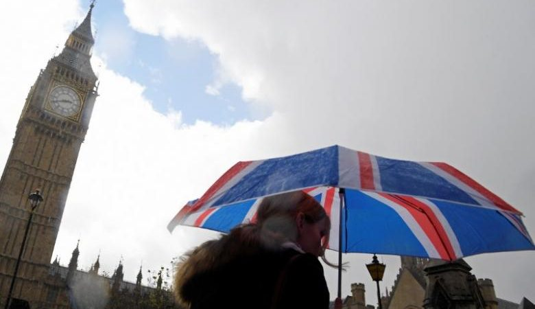 A woman carries a British union flag design umbrella as she walks past the Houses of Parliament in London, Britain, April 26, 2017. REUTERS/Toby Melville