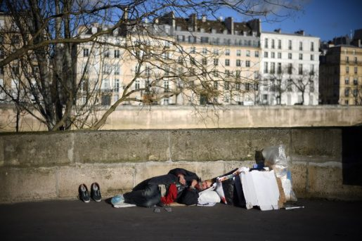 A homeless man sleeps along the river Seine in front of the Saint-Louis island in Paris, on December 28, 2017. / AFP PHOTO / Eric FEFERBERG