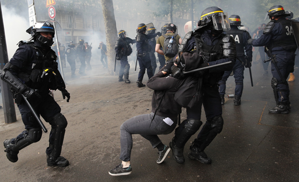 Riot police officers detain a protestor during a demonstration in Paris, Tuesday, May 22, 2018. French public services workers have gone on strike as part of their protest a government plan to cut 120,000 jobs by 2022. (AP Photo/Christophe Ena)