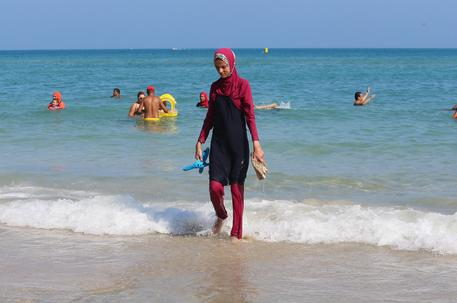 epa05513331 A Tunisian woman wearing a 'burkini' walks at beach Bizerte, north-eastern Tunis, Tunisia, 28 August  2016.  EPA/MOHAMED MESSARA